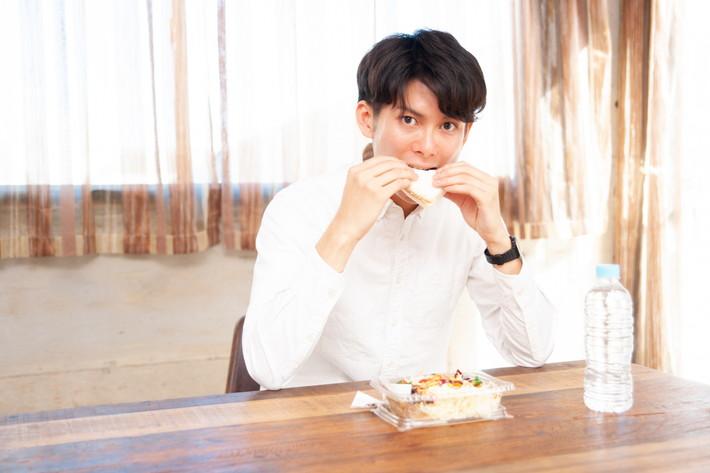 サンドウィッチを食べる男性